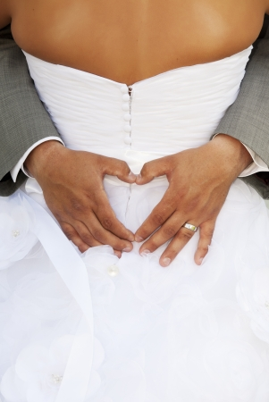 hands on waist: Groom making a heart sign while his arms are around his bride