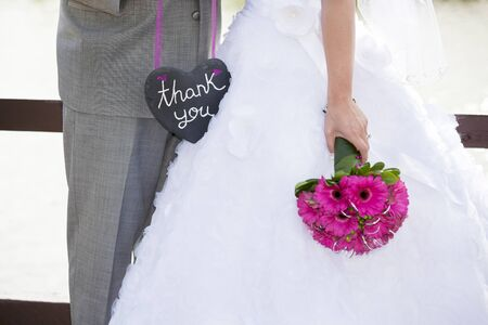 A bride and groom holding a heart shaped thank-you sign  photo