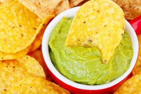 corn chip: Macro shot of a corn chip dipped in fresh avocado guacamole dip