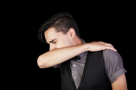 A young man sneezing into his elbow   Black background