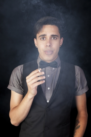 A young man holding a cigarette and blowing smoke straight at the camera  Stock Photo - 14942804