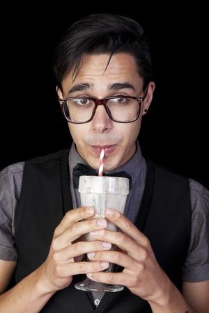 geeky: A geeky, nerd guy sucking chocolate milkshake through a straw  Stock Photo