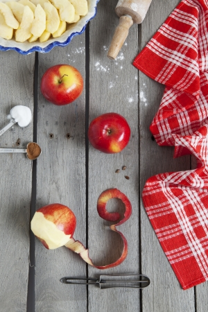 Apple pie ingredients on a raw, weathered wood background