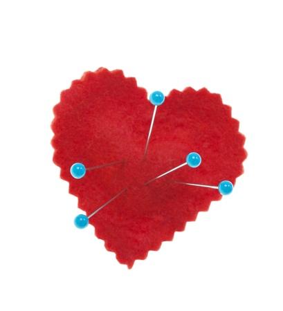 Corazón conceptual con alfileres clavados en ella, lo que representa el dolor del corazón, un corazón roto, o Shot vudú sobre fondo blanco Foto de archivo - 17312808