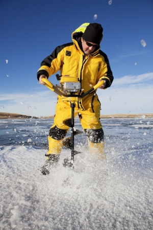 ice fishing: Ice flies everywhere as an ice fisherman uses an auger to make his fishing hole.