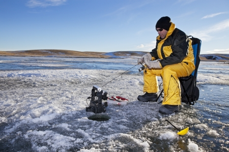 Man ice fishing on a frozen Canadian lake.