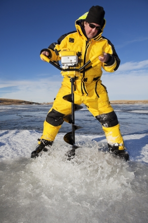 ice fishing: Water floods over the ice as an ice fisherman drills through with an auger to make his fishing hole