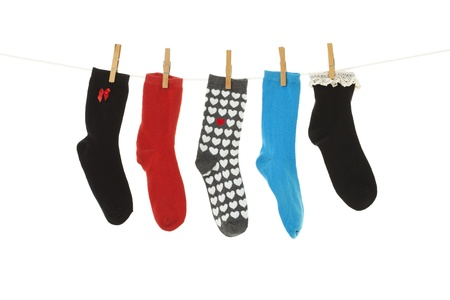 Odd socks whose mates have been lost, hanging on a clothesline   Shot on white background  Stock Photo