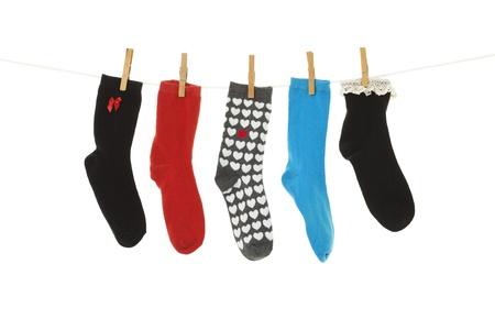 Odd Socken, deren Kumpels verloren gegangen sind, hängen auf einer Wäscheleine Schuss auf weißem Hintergrund