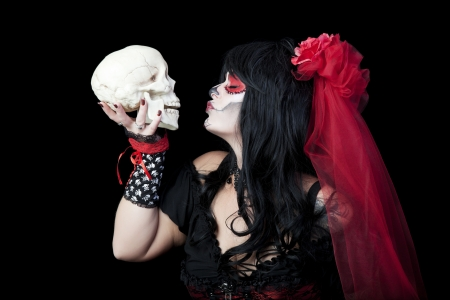 sugar veil: Day of The Dead   A woman dressed as a sugar skull kissing the skull of a departed love one