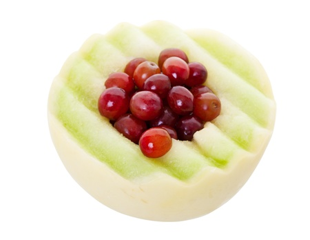 honeydew: Half of a honeydew melon stuffed with fresh red grapes   Shot on white background   With clipping path