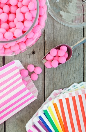 Old fashioned candy jar full of pink peppermints being distributed into individual candy bags