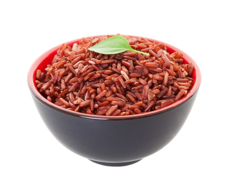 A bowl of Red Cargo Rice garnished with a single leaf of lemon basil   Shot on white background