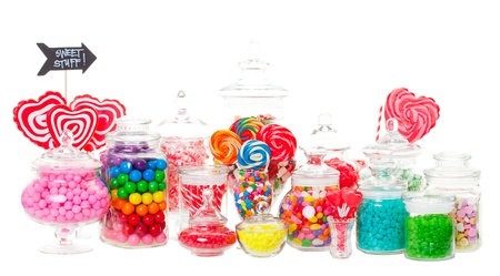 A candy buffet with a wide variety of candies in apothecary jars   Shot on white background  photo