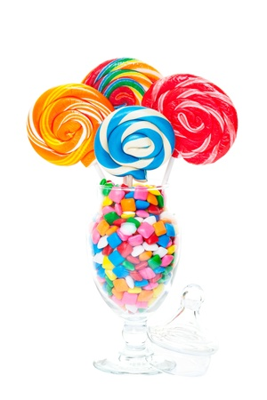 Large swirled lollipops displayed in an apothecary jar full of bubble gum   Shot on white background