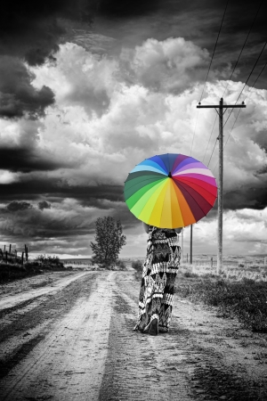 rainbow umbrella: A woman walks alone along old dirt road with ominous clouds above
