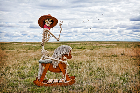 Skeleton cowboy riding a rocking horse in a field. Stock Photo