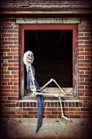 A female skeleton posing like a pinup girl in the window of an old abandoned home. Stock Photo
