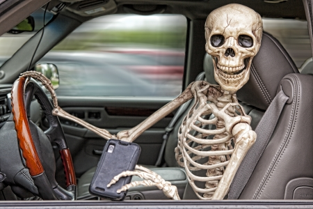 A skeleton behind the wheel of an SUV, distracted by his cell phone.  He is also not wearing a seatbelt. Imagens - 23213200