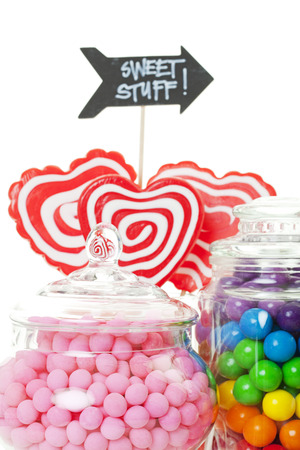 A closeup of part of a candy buffet with a variety of candies in apothecary jars.  Shot on white background. photo