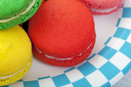 Closeup of brightly colored macaroon cookies on a plate edged in a blue and white checker. photo