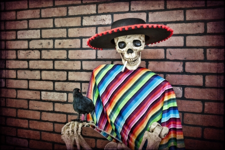 Latino skeleton sitting against a brick wall having a smoke with his trusty pet crow. photo