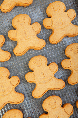cookie sheet: Macro of freshly baked gingerbread men on an antique cookie sheet. Stock Photo