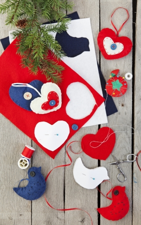hand crafted: Homemade Christmas ornaments being made from felt, ribbon, and buttons.