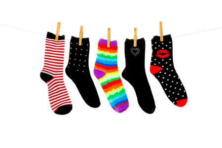unmatched: Odd socks whose mates have been lost, hanging on a clothesline.  Shot on white background.