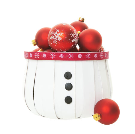 A snowman inspired basket bulging with a multitude of red Christmas balls on white background. Stock Photo