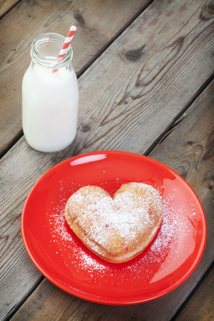A heart-shaped doughnut sprinkled with icing sugar on a red plate. photo