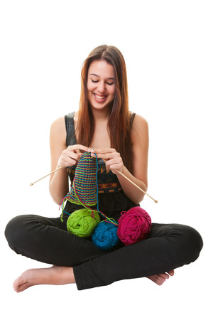 A young woman knitting a stripped scarf using three different colors of yarn.  Shot on white Background.