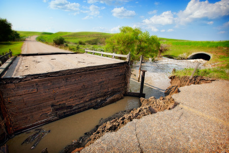 A road and bridge damaged by muddy, flood waters  photo