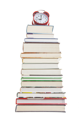 Clock on a stack of text books.  Shot on white background.