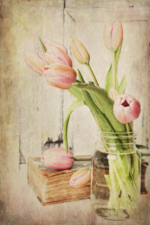 Fine art image of pink tulips in a jar next to a vintage book. Textured. Imagens