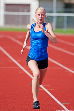 track and field athlete: A young girl running on a track towards the camera. Stock Photo