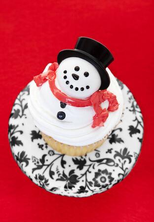 A cupcake decorated as a snowman on a cupcake pedestal.