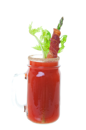 tomato cocktail: Caesar made with vodka and clamato juice, served in a spicy rimmed mason jar and garnished with fresh celery and asparagus wrapped in crispy bacon. Shot on white background. Stock Photo