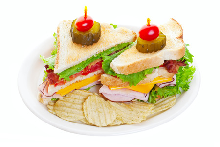 Clubhouse sandwich topped with a pickle and a baby tomato and served with potato chips on white background.