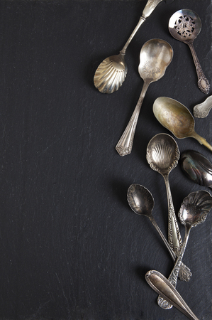 Antique spoons with various patina on a slate board. Imagens