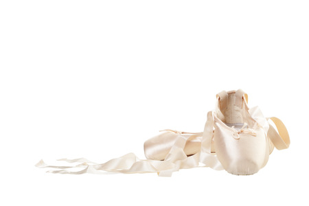 A worn pair of pink Ballet Slippers on white background.
