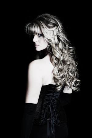 Portrait of a mysterious young woman dressed in formalwear.  Black background.