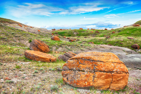 seven persons: The Red Rock Coulee landscape features round reddish, prehistoric boulders. These are sandstone concretions and at up to 2.5 m in diameter, they are among the largest in the world.  Southern Alberta, Canada.