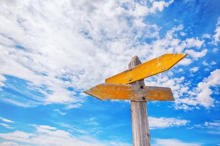 encruzilhada amarelas rústicas sinal contra um céu azul nebuloso.