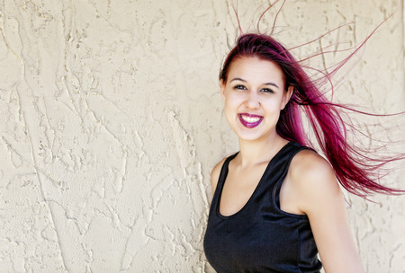 A young woman with her hair dyed magenta pink, blowing in the wind.
