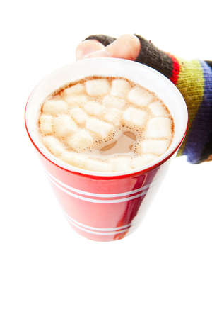 A mug of hot chocolate, complete with miniature marshmallows, held by a mittened hand. Shot on white background.