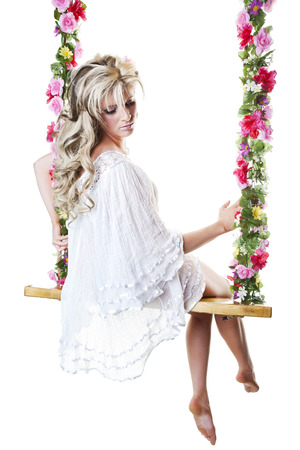 nightgown: Beautiful young blond woman in a flowing white nightgown, perched on a dreamy floral covered swing.  Shot on white background.