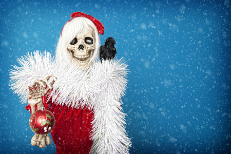 Happy Christmas skeleton holding a Christmas ball in snowy twilight.