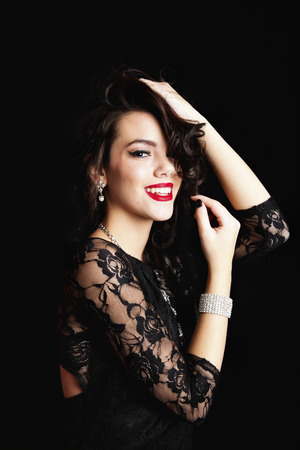wind blown hair: Smiling young woman wearing a classic black lace dress and crystal jewelery with hands up in her hair.  Shot on black background.