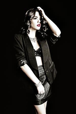 Beautiful lady with movie style glam girl fashion look.  Shot on black background.